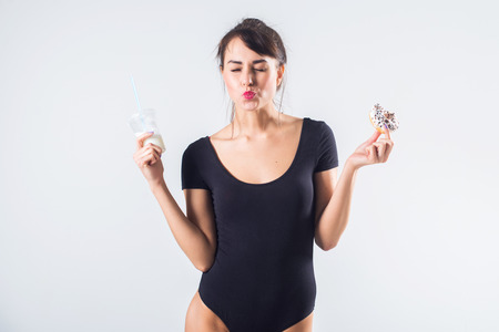 one: Young brunette model with cocktail and donut studio shot on white background, not isolated. Stock Photo
