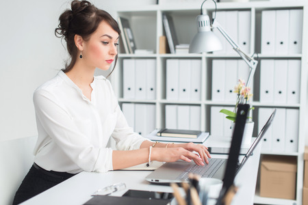 angle: Portrait of a young female office worker sitting at her workplace in office, typing, looking on laptop screen attentively