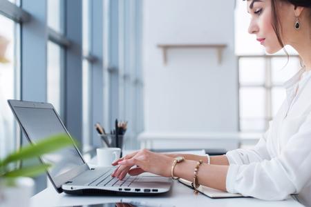 魅力的なメスの助手作業、入力、ポータブル コンピューターを使用して集中、モニターを見ています。オフィス ワーカーのビジネス ・ メールを読 写真素材