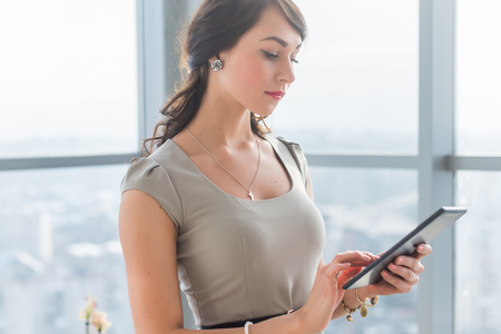 teleworker: Close-up portrait of a young attractive freelancer using tablet for telework, typing and reading new messages on-line Stock Photo