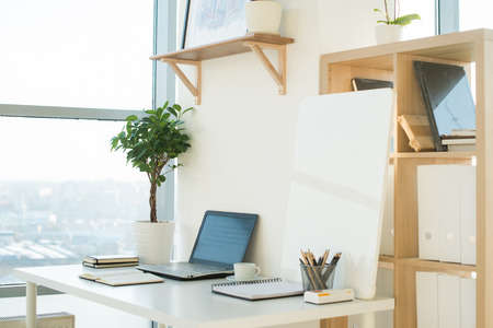 Side view picture of studio workplace with blank notebook, laptop. Designer comfortable work table, home office 스톡 콘텐츠