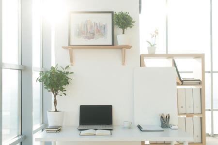 Vue latérale image du lieu de travail de studio avec cahier vierge, ordinateur portable. Designer table de travail confortable, bureau à domicile Banque d'images