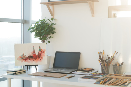 side order: Painter workplace in order side view. Designer desk with drawing equipment. Home studio for artist.
