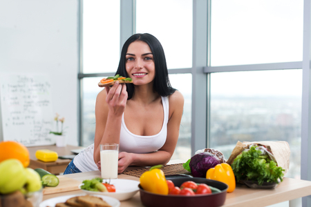 Close-up portrait of woman standing in kitchen, leaning on wooden table, having snack. Smiling girl maintains healthy lifestyle
