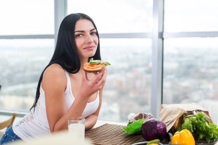 leaning: Close-up portrait of woman standing in kitchen, leaning on wooden table, having snack. Smiling girl maintains healthy lifestyle