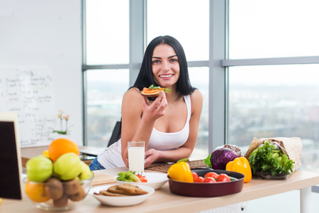 Close-up portrait of smiling woman eating diet vegetarian sandwich with vegetables for breakfast in morning, looking at camera