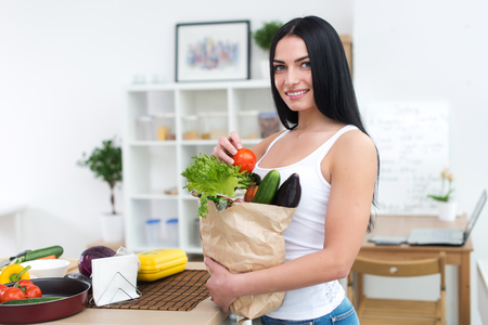 Female cook holding bag full of greens, just came back from market, ready to prepare healthy food with cookbook recipe, close-up front view portrait Stock Photo
