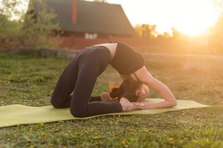 position: woman practicing outdoors meditating in yoga position Stock Photo