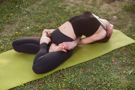 bends: woman practicing outdoors meditating in yoga position Stock Photo