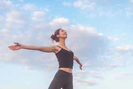 armonia: mujer disfrutando de la puesta de sol con los brazos abiertos y la cara levantada en el cielo.