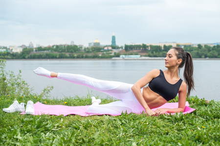 exercise: Woman in a yoga pose with her arm reaching overhead raising leg. Stock Photo