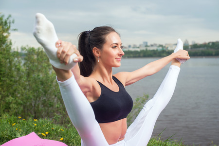 legs wide open: Woman holding legs apart doing exercises aerobics warming up with gymnastics for flexibility leg stretching workout outdoors