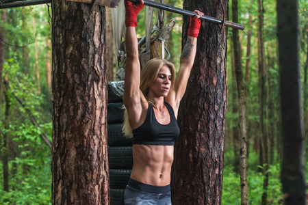 strong chin: Fit woman preparing to do pull ups on horizontal bar