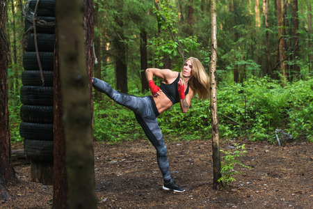 bout: Fit girl beat high leg side kick working out outdoors. Woman fighter exercising, doing kickboxing training martial arts.