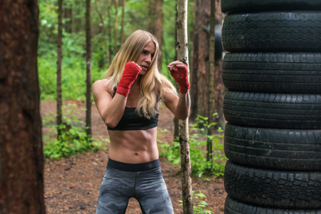 stance: Woman boxer professional fighter posing in boxing stance, working out outdoors Stock Photo