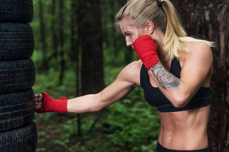 punched out: Portrait of girl boxer doing uppercut kick working out outdoors