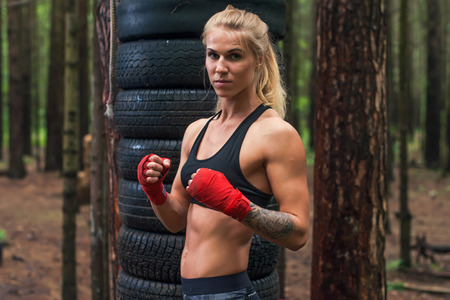 fit: Woman boxer professional fighter posing in boxing stance, working out outdoors.