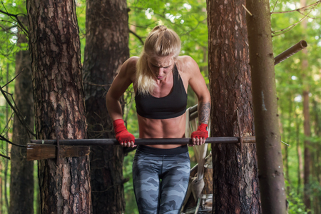Fit woman doing muscle up on horizontal bar. Stock Photo