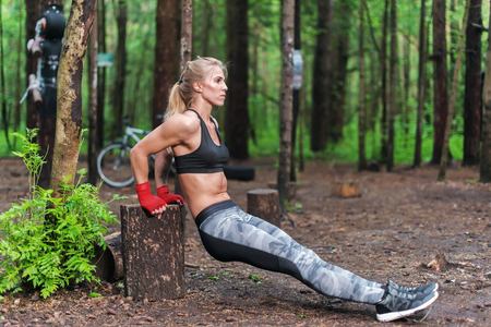 dips: Fit woman doing triceps dips at park. Fitness girl exercising outdoors with own bodyweight.