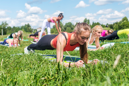 Fit woman doing plank exercise, working on abdominal midsection muscles. Fitness girl doing core workout in nature