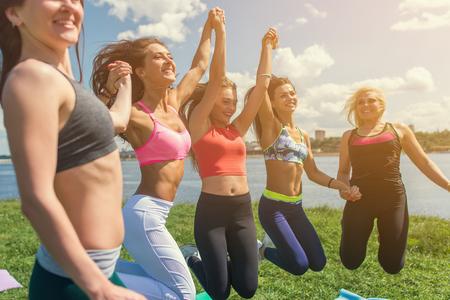 people jumping: Retrato de jóvenes amigos divertirse saltando en un día de verano.