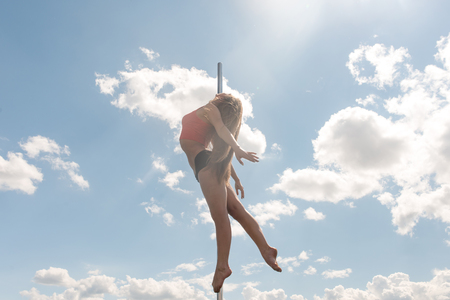 Pole dance fit woman exercising with pylon outdoors.