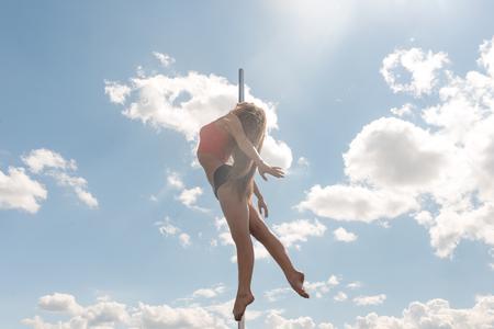 dances: Pole dance fit woman exercising with pylon outdoors.
