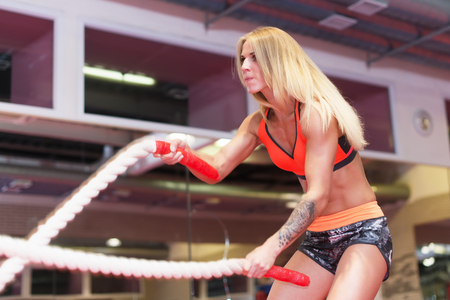battling: Fit woman working out with battle ropes at a gym