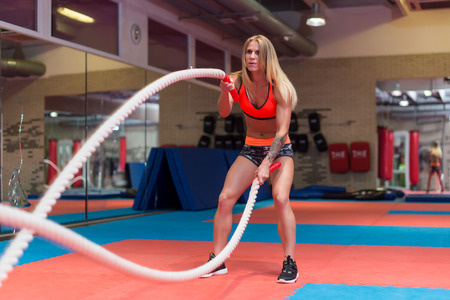 Fit woman working out with battle ropes at a gym