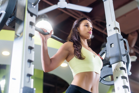low: Fit woman doing squats with the barbell Smith machine in the gym