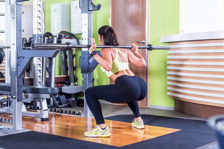 nalga: Ajustar mujer haciendo sentadillas con pesas en el gimnasio Foto de archivo