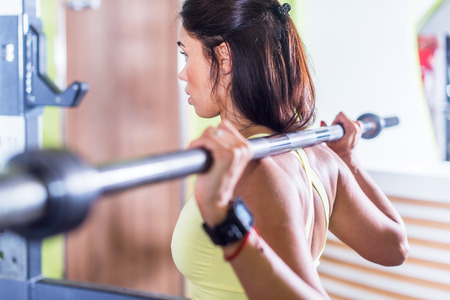 squat: Fit woman doing squat with barbell in the gym