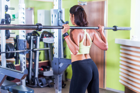 culo di donna: Fit woman exercising with barbell in shoulders