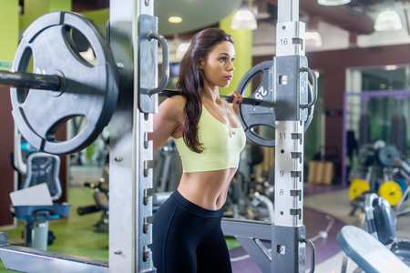 squats: Fit woman doing squats with the barbell Smith machine in the gym