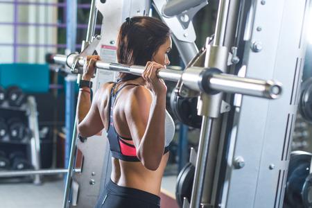 フィットの女性ジムでスミスマシンのバーの重量で肩プレス運動を行う