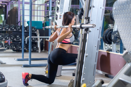 lunges: Fit girl doing lunges with the smith machine.