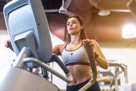 eliptica: Ajustar mujer haciendo ejercicio en una bicicleta elíptica
