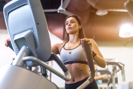 Fit woman doing exercise on a elliptical trainer 版權商用圖片 - 62379871