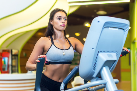 Woman exercising at the gym in an elliptical trainer Cardio training Stock Photo