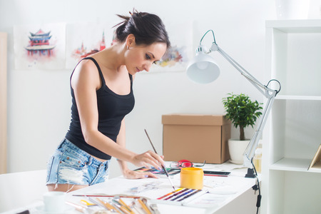 Side view portrait of a happy artist at the workplace. Young woman with paintbrush. photo