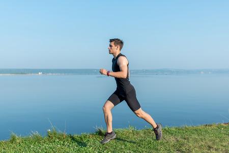 running man: Athlete running man jogging on beach. Morning workout in summer.