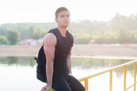 sportive: Portrait of athletic man sitting on pier near pond.
