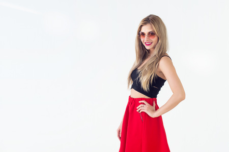 unbound: Young blond model presenting new fashionable summer look, wearing circle sunglasses, red skirt and black sleeveless top close-up front view portrait Stock Photo