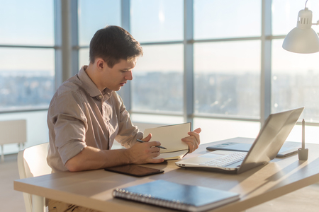 Man freelancer writing on notebook at home or office
