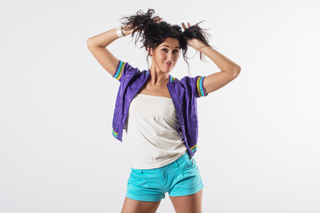 clowning: Young happy girl holding her hair, imitating tails hairstyle, wearing trendy outfit.