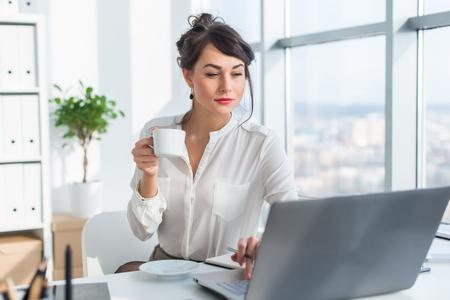 personen: Jonge vrouwelijke ondernemer werkzaam in het kantoor met behulp van laptop, het lezen en zoeken informatie aandachtig, het drinken van koffie