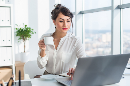 persons: Young female business person working in office using laptop, reading and searching information attentively, drinking coffee Stock Photo