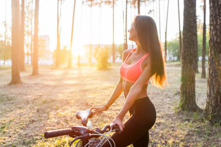 woman sunset: Fit woman standing with bicycle in park enjoying sunset Stock Photo