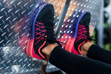 powerlifting: Close up shoes of a fit young woman doing leg press in the gym.