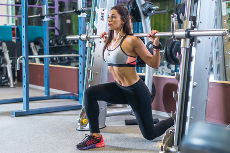 sport woman: Fit girl doing lunges with the smith machine.
